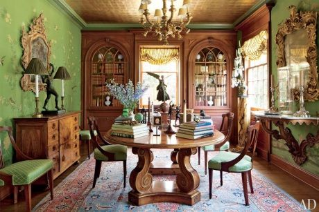 Timothy Corrigan's dining room in his home in Los Angeles has green, yellow and gold Chinoiserie silk wall panels. An oriental rug in soft blue and pale bluish red is not color coordinated, and evokes old world style. Gold teapaper on the ceiling adds a glamorous touch. Image courtesy Architectural Digest.