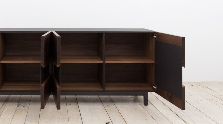 Shown in clarowalnut withblackened steel base and door panels, 84x 20 x 25H DESCRIPTION Two opposing slabs and steel plate create the dynamic front of this media unit. Doors on either side frame two center drawer units or custom storage arrangements. The surrounding frame is finished in a crisp black lacquer, and the unit rests …