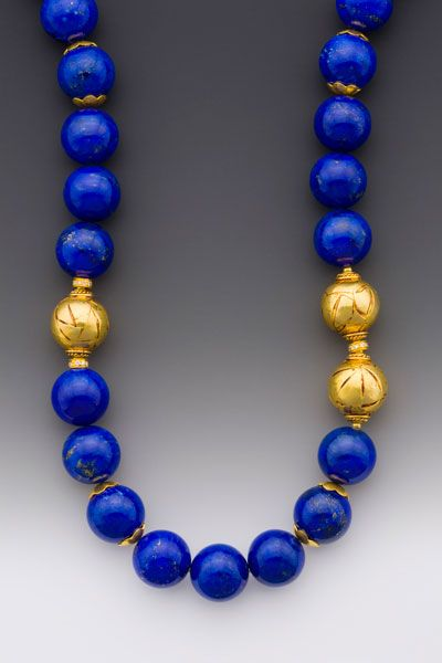 Rhapsody: A necklace of 14mm Afghani lapis beads with three offset 14mm 18K beads flanked by 18K accents with diamond rondelles. Large 18K clasp