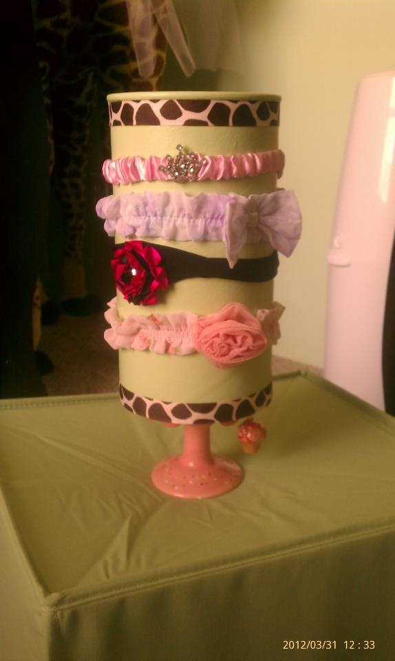"Baby Headband Holder made from oatmeal canister. top left open to hold brushes and other hairpieces. Strip, paint, and ribbon embellishment added around top and bottom. ""Cupcake"" pedestal from #HobbyLobby glued to bottom for height."