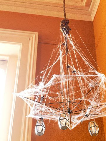 Recycle an old umbrella as a haunting light fixture. Remove the fabric covering, then stretch spider webbing over the frame. Decorate with plastic spiders and battery-operated lanterns attached to the wire with S hooks. Tie rope around the handle and hang from the ceiling with a plant hook.
