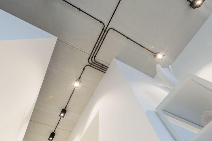 In plaats van een verlaagd plafond te maken heeft BNLA architecten de elektra leidingen in het zicht gelaten. Het leidingschema werd zo ontworpen dat er een fraai patroon op het plafond ontstond. Op deze wijze konden alle buizen in het zicht gelaten worden. Om een krachtig beeld te krijgen is er gekozen voor zwarte elektra buizen met zwarte opbouwspots. Fotografie Wim Hanenberg.