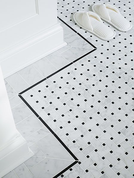 Basketweave marble floor tile, framed by a pencil-thin ceramic border, is warmed by an electric heat mat.