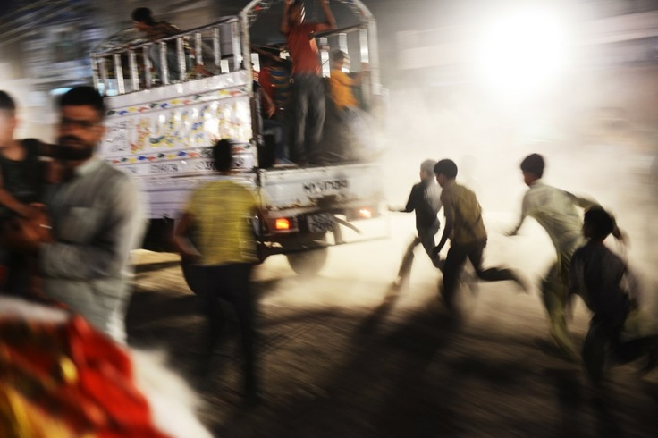 Lahore, Pakistan May 9, 2013 Pakistani boys run after a truck distributing election flags during a political rally on the last day of the election campaign.