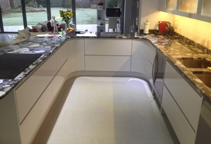 Contemporary kitchen from Anthony Mullan furniture. High-gloss white Parapan with curved cabinets to suit the design.