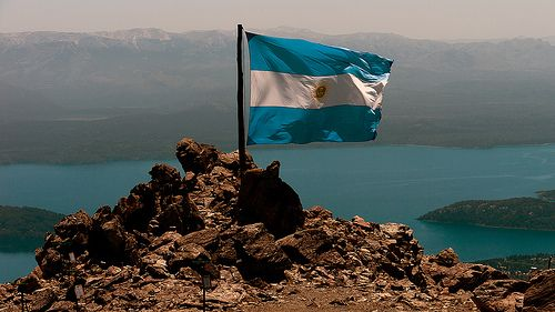 Argentine flag. In the background, Nahuel Huapi lake (765 m) covered in an ash cloud from Puyehue volcano. Refugio Lynch (1930 m), Cerro Catedral, Bariloche, Río Negro, Argentina, 2011-12-06 12:00.