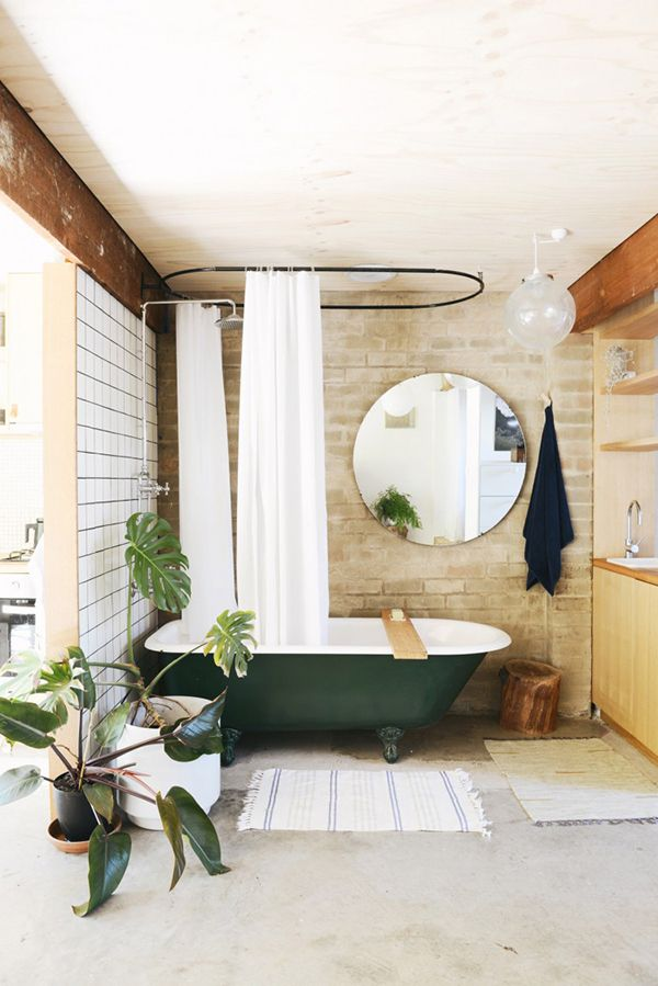 Coup de coeur pour cette salle de bain ouverte. On aime tout particulièrement la baignoire sabot de couleur vert sapin assortie aux plantes et le grand miroir rond #decoration #urbanjungle #bathroom