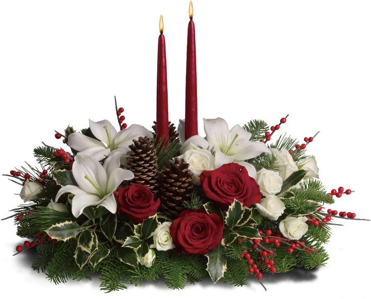 Arranjo central natalino. Rosas vermelhas e brancas são misturadas com o nobre abeto, o festivo pinho branco, e variegada azevinho debaixo de duas velas vermelhas. Bagas vermelhas e pinhas aumentam a beleza do Natal.  Fotografia: Teleflora.com.