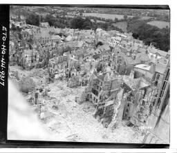 Photo shows the blasted ruins of Coutances … 29/07/44 = [Quartier sud-ouest de la ville partiellement détruit par les bombardements et vu depuis une tour de la cathédrale].
