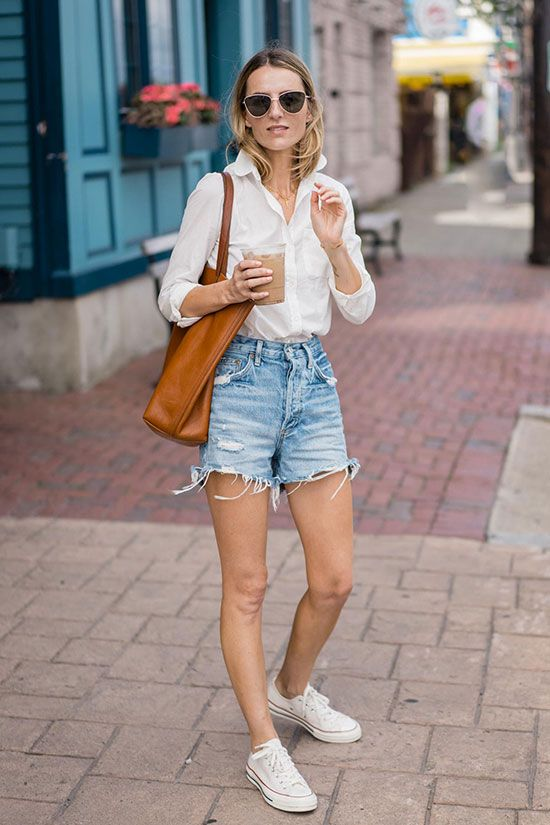 Fashion blogger Jess Kirby wearing a white shirt, denim shorts, white converse sneakers, metallic sunglasses and a brown tote bag. Summer outfit, summer style, summer uniform, minimal style, minimalism, classic style, simple outfit, beach outfit, vacation outfit, denim shorts outfit, easy outfit, spring outfit,