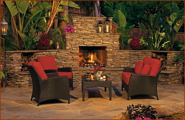 Stone outdoor fireplace with tropical landscaping and rustic seating with red accents