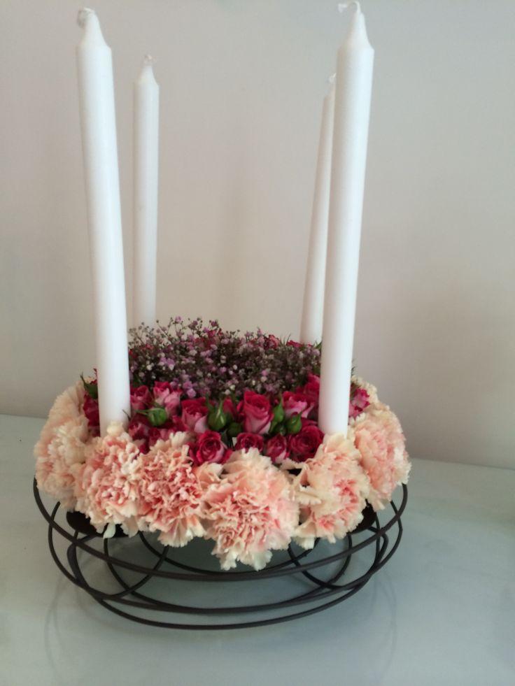 Centrotavola in ferro battuto, con ghirlanda di garofani salmone, roselline fuxia e gypsophila rosa