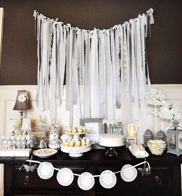 – Fabric streamer backdrop featuring five different fabrics & lace  – Marvelous, homemade mini cupcakes tower + other pretty sweets  – Hand-made yarn daisy garland, tissue poms & bunting cake topper
