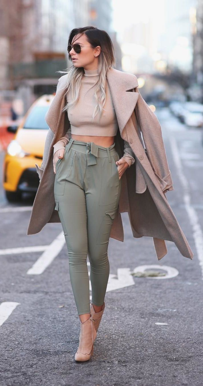 A crop top, high-waisted trousers, long coat, and neutral heels.