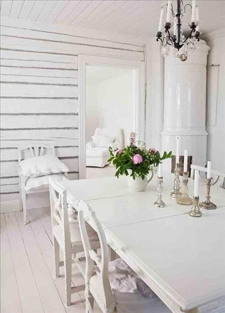 På en av väggarna i matsalen har man låtit byggtimret vara synligt och målat det vitt. Bordet och de udda stolarna är vitmålade loppisfynd. I taket hänger en ljuskrona från Housedoctor som Sofie säljer i sin butik. På bordet blommor från trädgården i en gammal mjölkkanna och en samling udda ljusstakar.