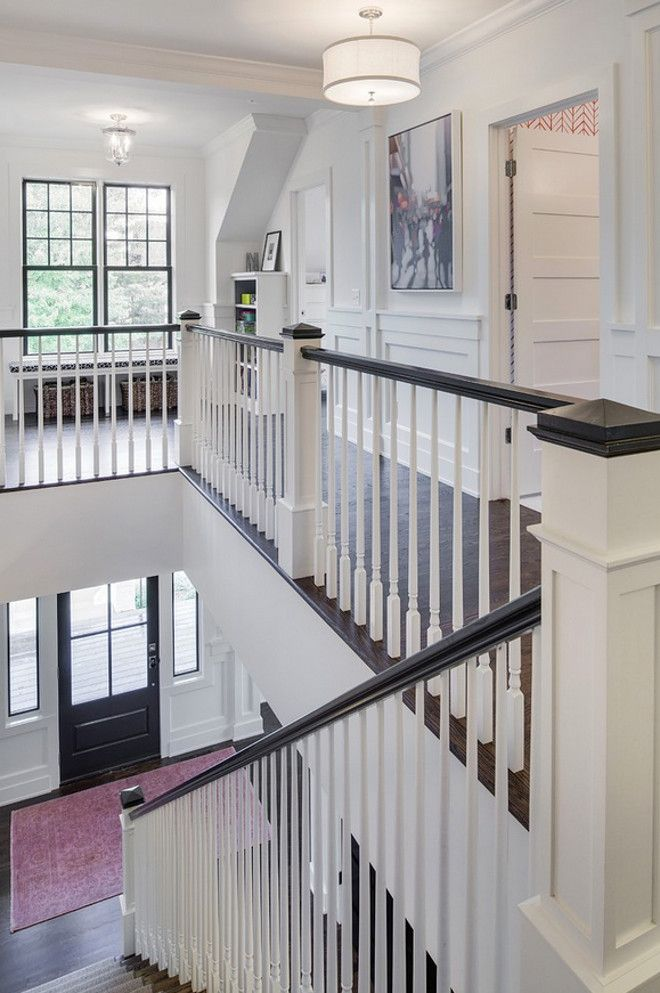 gorgeous black and white staircase and hallway with detailed mouldings, white walls, black window trim.