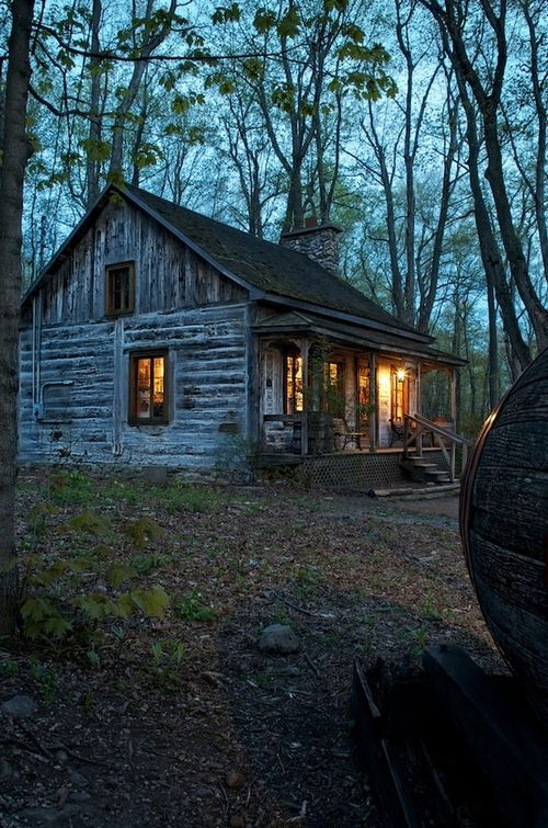 Simple cabin in the woods provides a warm welcome -- looks like the American south or Appalachia.