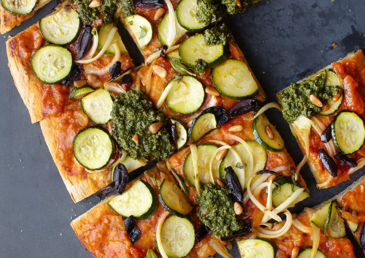 <p>Thin slices of zucchini stand in for mozzarella, while onions, kalamata olives, pine nuts, pesto, and fresh basil give this Summer Pesto Pizza more than ample flavor and variety.</p>