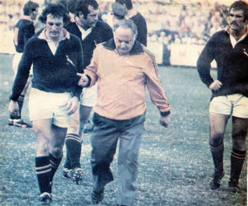 24 July 1976 - South Africa 16 / All Blacks 7 Here is Gerald Bosch being led off by the Springboks team doctor Jack Sweidan –to be replaced by De Wet Ras- 10 minutes before the end. The Springboks gambled heavily with Bosch in this test and he could not do himself justice missing with 5 normally easy penalties for him and with the conversion of Krantz's try –which hit the upright- and two drop goal attempts. Those long kicks deep to the corners driving the opposition back on their heels were…