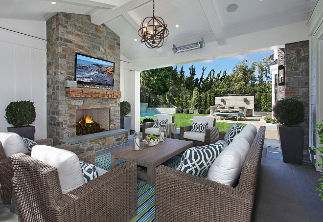 Covered Patio loggia ideas. What an inviting space! This loggia features a cozy seating area and board and batten walls flanking an outdoor fireplace. Notice the reclaimed wood mantle. #loggia #coveredpatio #outdoorfireplace Patterson Custom Homes. Interiors by Trish Steele of Churchill Design.