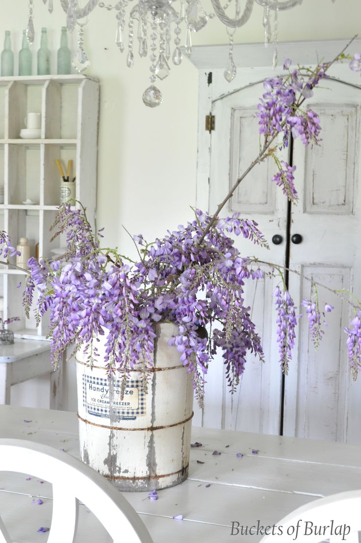Vintage ice cream bucket with purple wisteria. Farmhouse, white cabinet, farmtable. Dining room, chandelier, fresh flowers. Spring table setting. Buckets of Burlap blog and home.