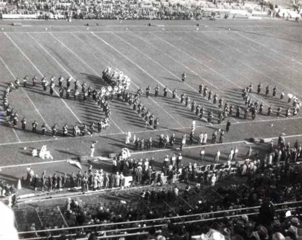 """This  photograph shows the first Script Ohio, which was done at Ohio Stadium October 10, 1936. In its earliest performances, a trumpet player """"dotted the I"""" of the formation, but this honor quickly fell instead to a sousaphone player for a more dramatic finish. Known as """"The Best Damn Band in the Land"""" (TBDBITL), the Ohio State University Marching Band originated as a 12-piece fife and drum corps in 1878."""