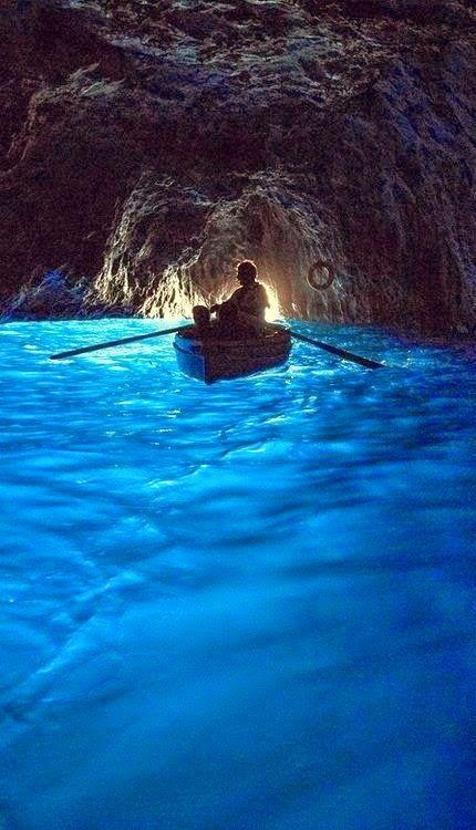 The Blue Grotto, Capri Italy. The sunlight shines in a cave with a small opening, reflects off the white sand then up thru the water.