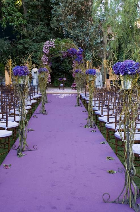 A raised aisle features a beautiful lavender runner and floral pedestals wrapped in vines.