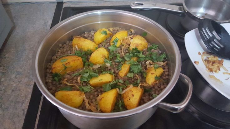 Step 1: Layering of Briyani - marinated chicken with yogurt and spices, par-boiled lentils, fried onions, potatoes and coriander.