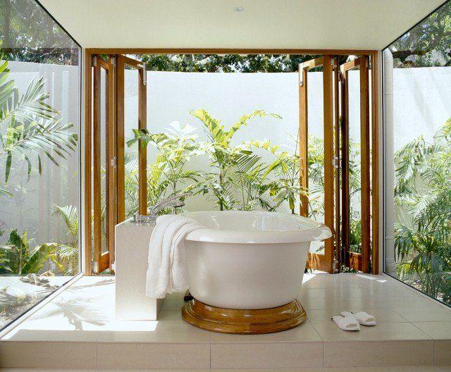 une baignoire blanche et moderne avec une vue sur le jardin vert