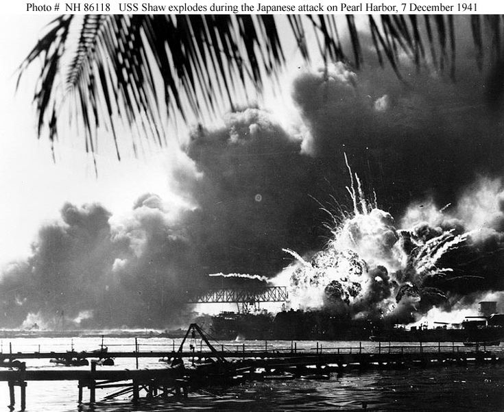 Pearl Harbor Attack, 7 December 1941 The forward magazine of USS Shaw (DD-373) explodes during the second Japanese attack wave. To the left of the explosion, Shaw's stern is visible, at the end of floating drydock YFD-2. At right is the bow of USS Nevada (BB-36), with a tug alongside fighting fires. Photographed from Ford Island, with a dredging line in the foreground.
