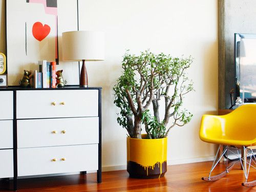 STILL love this room.  From the brass bookends, to the paint dipped planter (and the plant in it), to the yellow mod rocking chair. eclectic bedroom by Dabito