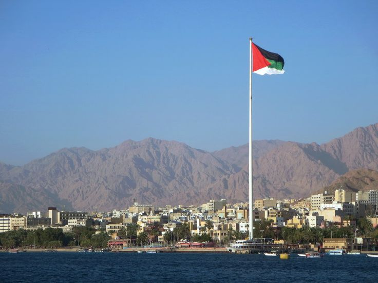 The Jordanian flag flutters proudly from the Arab Revolt Flagpole at Aqaba, Jordan, in plain sight of Eilat, Israel.