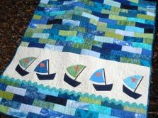 Cute baby quilt, but I also just generally like the idea of a quick pieced top with one band of applique across the width.  Faster than appliquéing a whole quilt of cute sailboats!