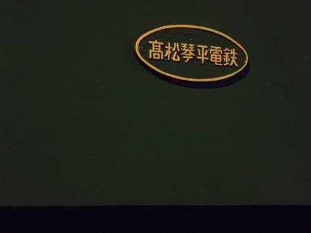 踏切の明かりに浮かび上がる、社名のプレート。濃緑の車体に少し古風な漢字が似合う。今日の短い旅を楽しいものにしてくれた、鉄道。[2011/8 瓦町駅 高松琴平電気鉄道長尾線 夜間滞泊列車(1200形)]© 2010 風旅記(M.M.) 風旅記以外への転載はできません...