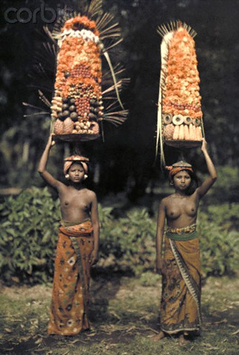 Bali, Indonesia --- Two Balinese women carry temple offerings of fruit on their head --- Image by © Franklin Price Knott/National Geographic Society/Corbis