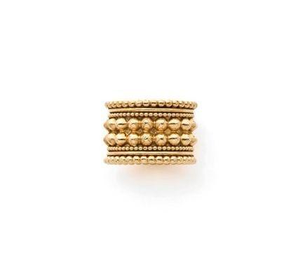 RENE BOIVIN Bague en or jaune formée d'un anneau large à décor clouté entre des filins unis ou perlés. Signée René Boivin. Poinçon du joaillier. Vers 1950.