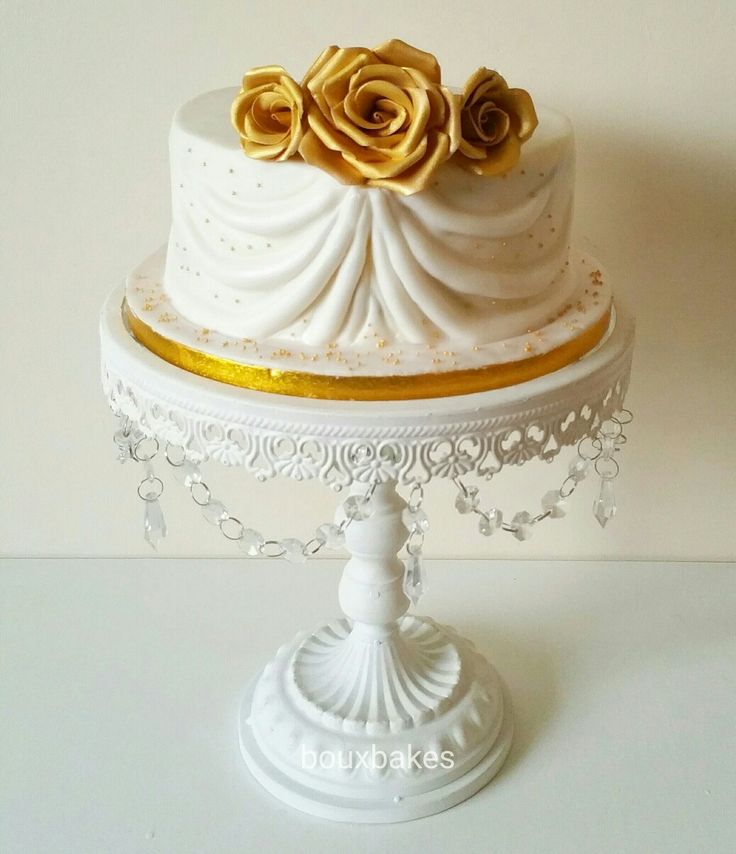 White and Gold fondant covered cake topped with gold sugar rose