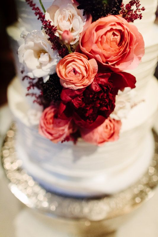 the wedding cake was adorned with a cascade of pink, white and burgundy wedding flowers, including garden roses, peonies, astilbe and ranunculus.