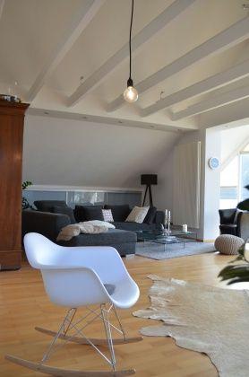 Mecedora Eames, Alfombra de piel de vaca en blanco, piso de parquet y vigas expuestas en el techo.