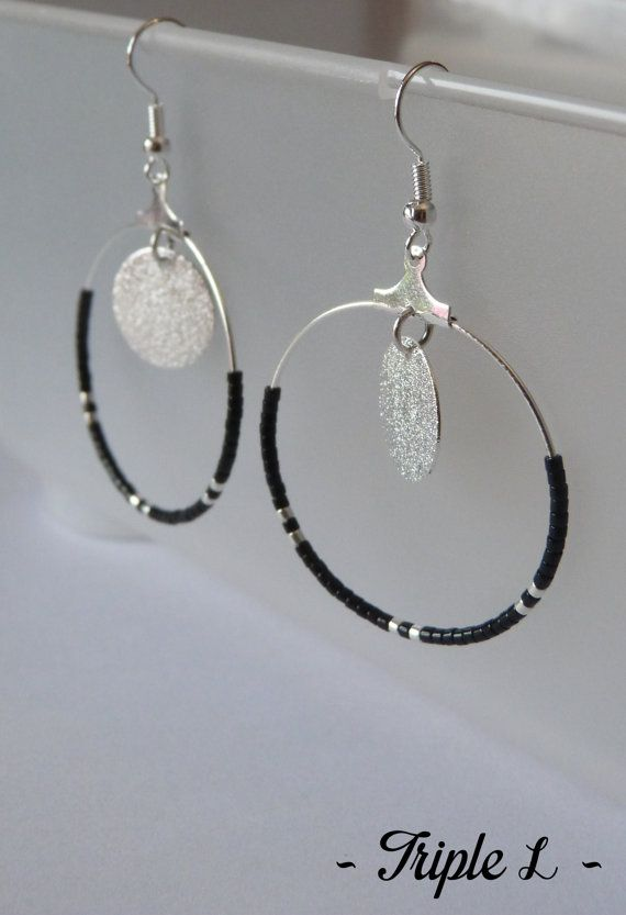 ~ DESCRIPTIF ~ Cette paire de boucles doreilles LINE est composée de créoles, de perles et dune monture en métal argenté pour oreilles percées. Couleurs des perles : noir - argenté. Dimensions : 3,5 cm de diamètre. ~ MATERIEL UTILISE ~ - Crochets doreilles en laiton argenté - Créoles en laiton argenté - Perles  ~ ENVOI ~ Les bijoux sont envoyés en courrier suivi dans une enveloppe en papier bulle et soigneusement emballés.  ~ PRECAUTIONS DUSAGE ~ Ce bijou est fait à la main et avec soin. Les…