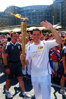 Gay soccer organizer Chris Basiurski helps carry Olympic torch through London