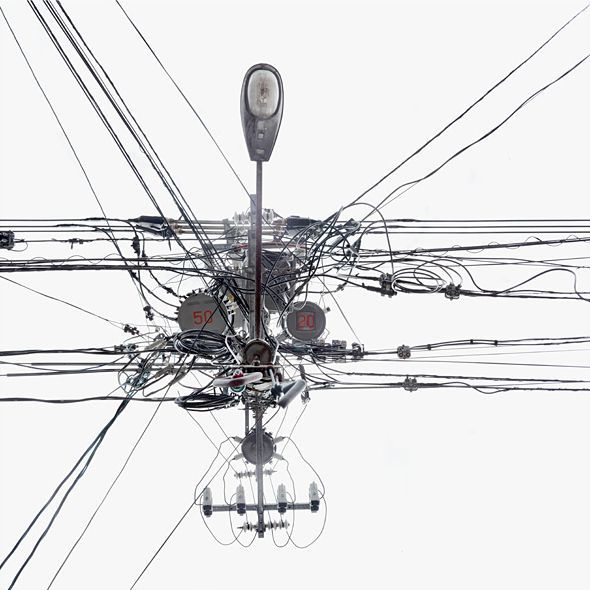 Gefeller takes at least two shots of utility poles vertically from below. In the subsequent digital composite the poles disappear, and the innumerable cables and transformers are converted into an abstract composition