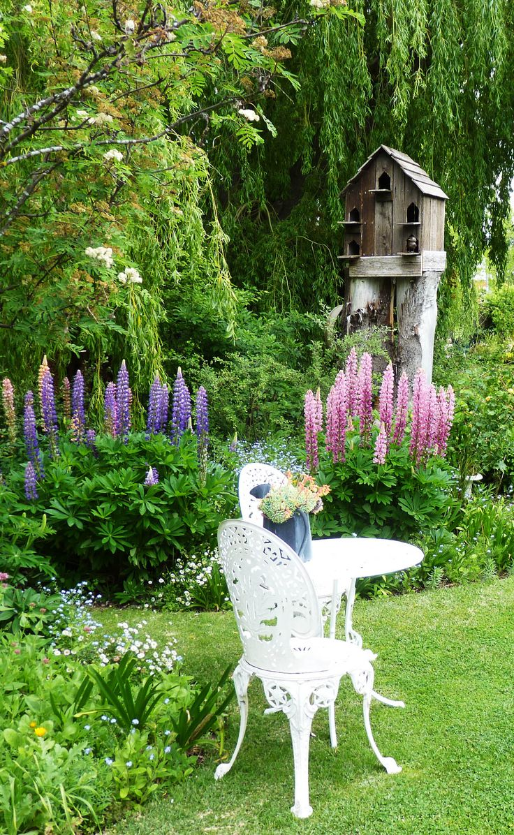 A country garden in Tasmania. Love the white iron bistro set and the big bird house.