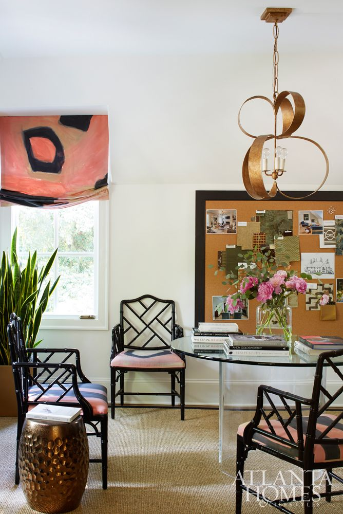 Chic home office features a gold chandelier illuminating a round glass table surrounded by black bamboo arm chairs and a copper hammered stool placed atop a