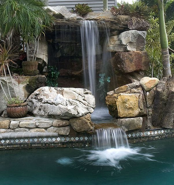 Natural stone swimming pool waterfalls top ten grotto for Natural rock swimming pools