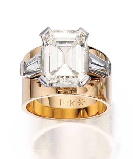 14 KARAT GOLD, PLATINUM AND DIAMOND RING Centered by an emerald-cut diamond weighing approximately 4.65 carats, flanked by two tapered baguette diamonds weighing approximately 1.00 carat, upon a polished gold band ring