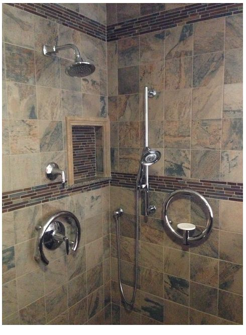 This shower has it all - beautiful tile, modern grab bars, shower wand as well as shower head, lever handle and recessed nook for shampoo & soap!