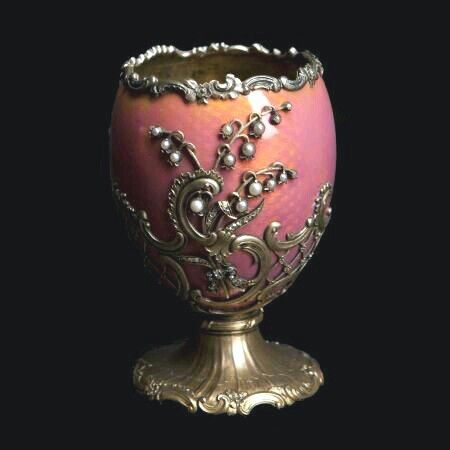 "Half-egg covered in translucent pink enamel on a guilloché background with pearl appliqués in the shape of lilies of the valley and diamonds. It was created at the same time as, and resembled, the egg given by Nicholas II of Russia to his wife, the Empress Alessandra Feodorovna, at Easter 1898, and known as ""The Lilies of the Valley Egg"". Both eggs have an identical floral decoration which employs the same materials, chosen to please the Empress, her favourite flowers being lilies of the…"