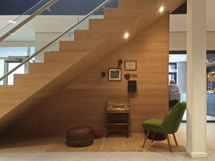 Knusse leeshoek met vintage elementen onder de trap. Kast als achterwand voor de bibliotheek Losser. Interieurontwerp door Evelien Lulofs voor 't Trefhuus: het Kulturhus in Overdinkel.